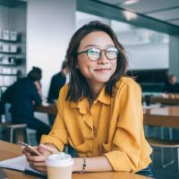 Portrait of cheerful hipster girl in optical spectacles for provide eyes protection looking at camera and smiling during blogging time in university classroom, concept of browsing and networking
